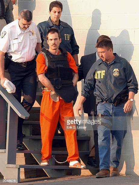 Multiple bombing suspect Eric Robert Rudolph center is escorted by law enforcement officials from the Cherokee County Courthouse and Jail in Murphy...