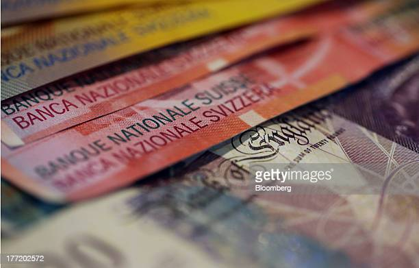 Multiple denomination Swiss franc bank notes sit with a British twenty pound note in this arranged photograph in London, U.K., on Thursday, Aug. 22,...