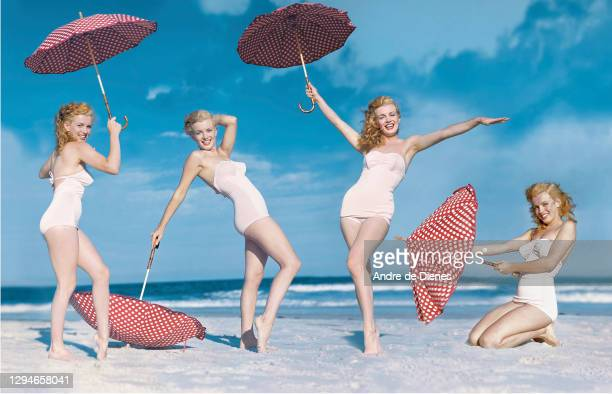 Multiple exposure image of American actress and model Marilyn Monroe , in a white swimsuit, as she poses with a red, polka dot umbrella on Long...