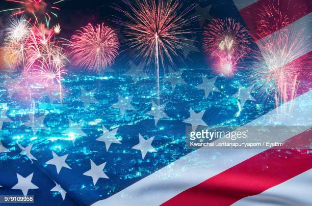 Multiple Exposure Of American Flag And Fireworks With City In Background