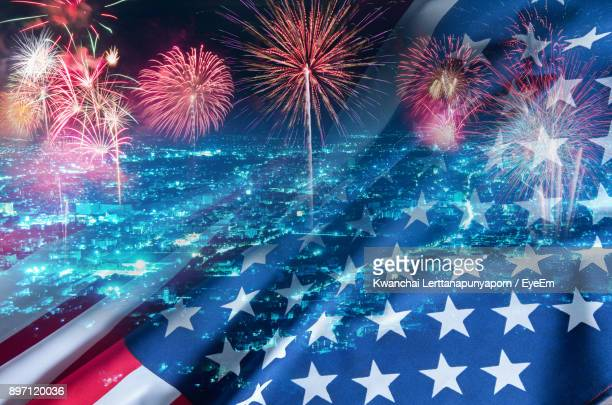 Multiple Exposure Of American Flag With City And Firework Display At Night