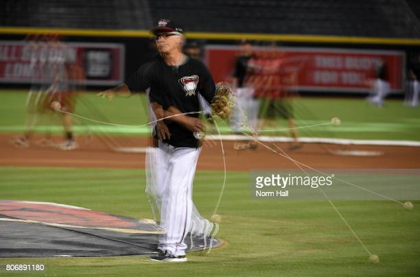 A multiple exposure of first base coach Dave McKay of the Arizona Diamondbacks uses a ball on a string to warm his arm up prior to throwing batting...