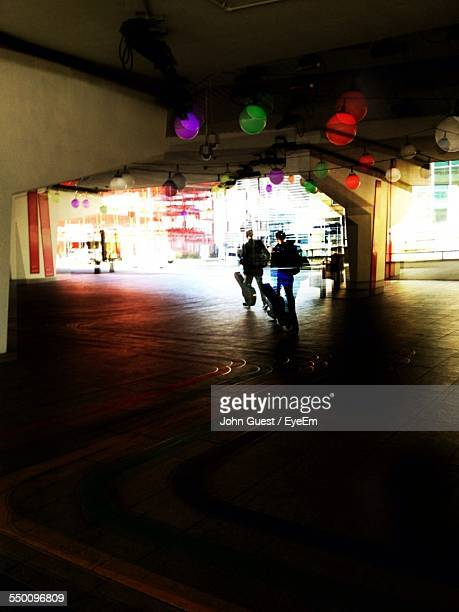 Multiple Exposure Of Man With Guitar Walking Under Bridge