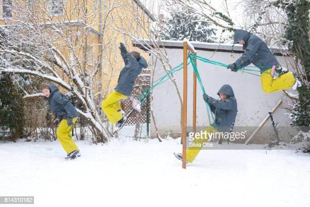 Multiple exposure of teenage boy swinging on swing in winter