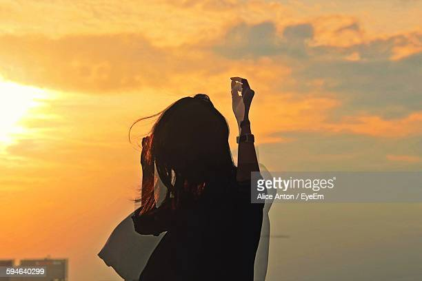 Multiple Exposure Of Woman Gesturing While Standing Against Cloudy Sky During Sunset
