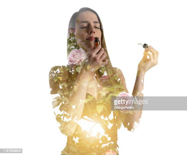 multiple exposure of young woman smelling essential oils and rose bush - aromatherapy oil stock pictures, royalty-free photos & images