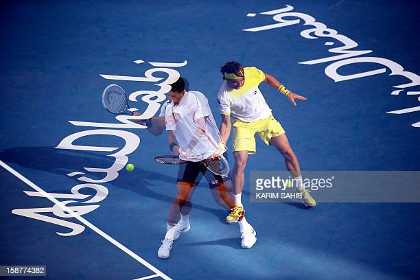 Multiple exposure picture shows world number one tennis player, Serbia's Novak Djokovic , and Spain's David Ferrer competing during their Mubadala...