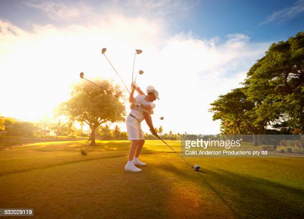 Multiple exposures of Caucasian golfer hitting ball on course