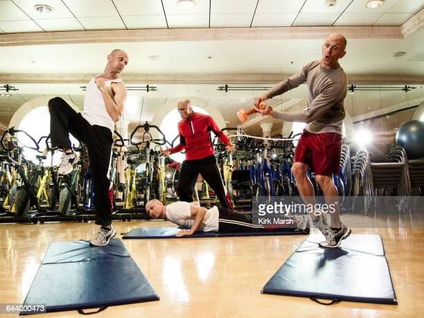 Multiple exposures of man working out with trainer
