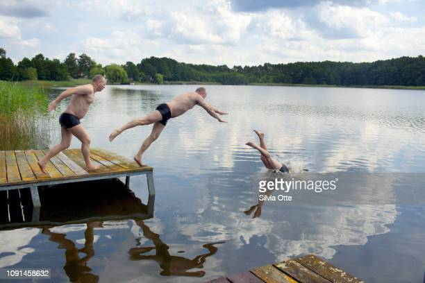 Multiple Exposures of middle aged man diving from jetty into lake with blue skies
