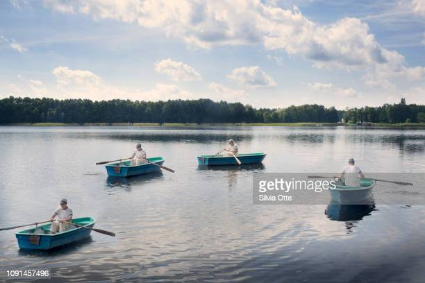 Multiple Exposures of middle aged man rowing a boat on lake with blue skies