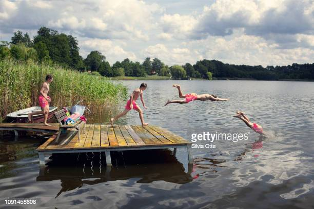 Multiple Exposures of teenage boy diving from jetty into lake with blue skies