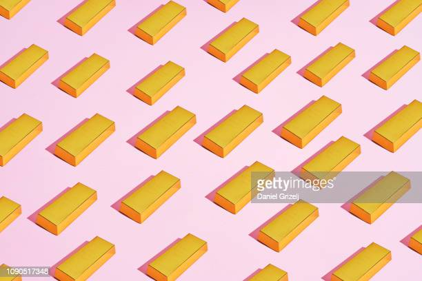 multiple gold bars placed in a pattern on a colored background - gold bars stock photos and pictures