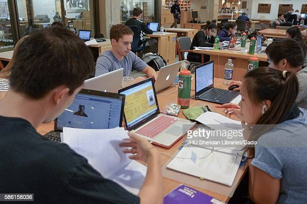 Multiple groups of college students sit together at tables in the Milton S Eisenhower Library at Johns Hopkins University, studying from notebooks...