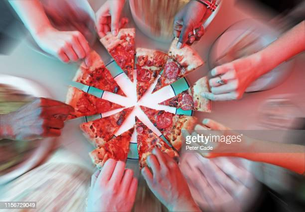 multiple hands reaching for pizza slices - reaching stock pictures, royalty-free photos & images