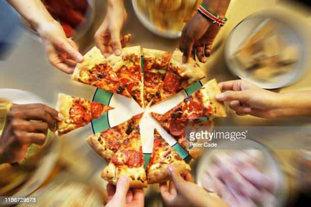 multiple hands reaching for pizza slices - medium group of people stock pictures, royalty-free photos & images