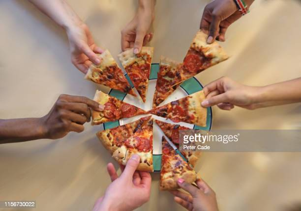 multiple hands reaching for pizza slices - teilen stock-fotos und bilder