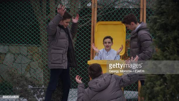 multiple image of boy by yellow garbage can against chainlink fence - chilly bin stock photos and pictures