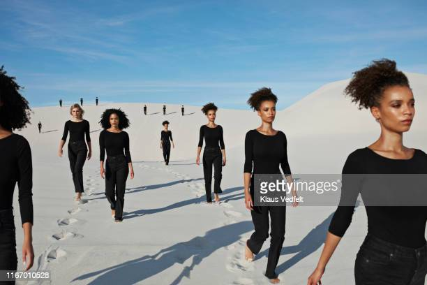 multiple image of confident young female models walking at desert - repetition stock pictures, royalty-free photos & images