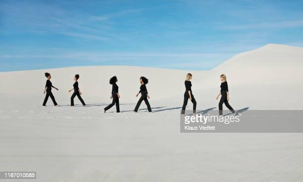 multiple image of female models walking at white desert against blue sky - hot female models stock pictures, royalty-free photos & images