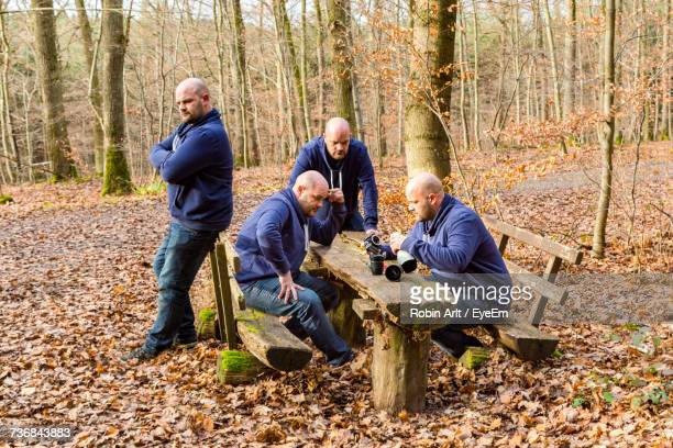 Multiple Image Of Man At Table In Forest During Autumn