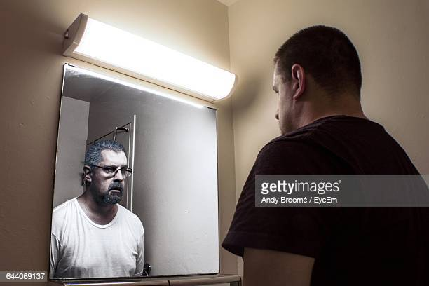 Multiple Image Of Man Looking At Mirror Reflection In Bathroom