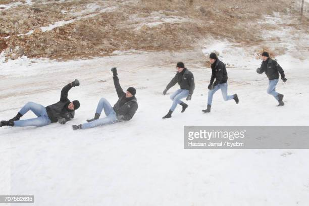 Multiple Image Of Man Sliding On Snow Covered Field