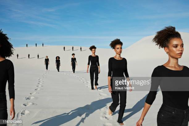 multiple image of young female models walking at desert - repetition stock pictures, royalty-free photos & images