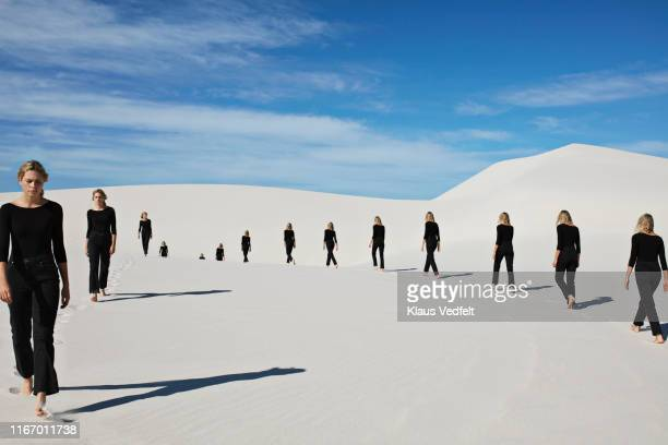 multiple image of young woman walking on sand at desert - repetition stock pictures, royalty-free photos & images