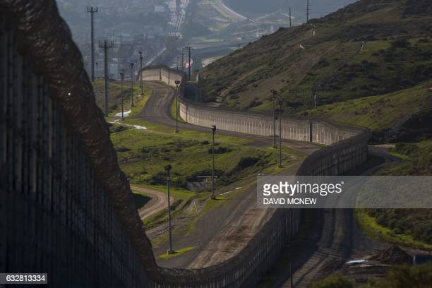 Multiple layers of steel walls fences razor wire and other barricades are viewed from the United States side of the of the USMexico border on January...