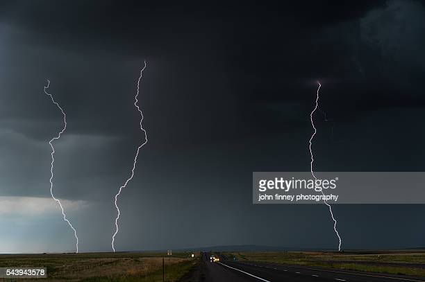 Multiple lightning strikes over a highway. McClave, Colorado, USA
