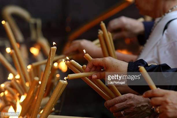multiple pairs of hands lighting gold candles - pilgrimage stock pictures, royalty-free photos & images