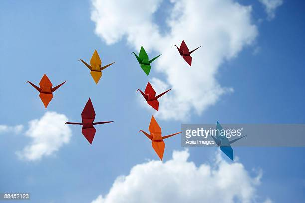 multiple paper cranes against sky backdrop