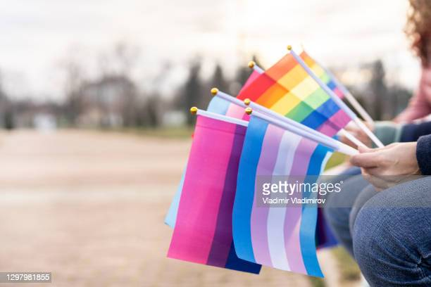 multiple pride flags hold by people - pride flag stock pictures, royalty-free photos & images
