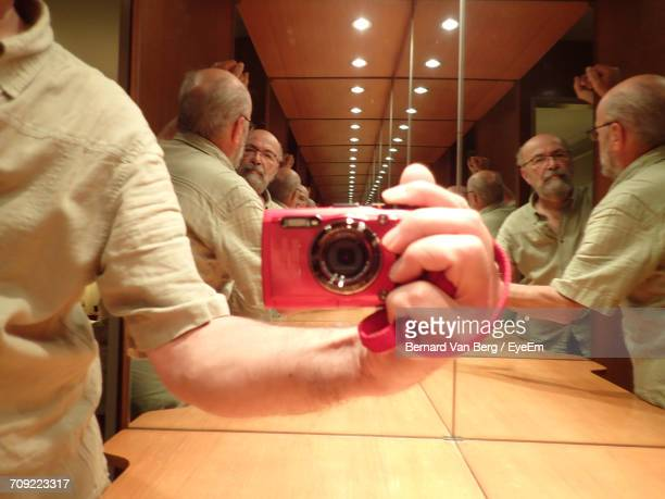Multiple Reflection Of Senior Man Taking Selfie Through Camera In Restroom