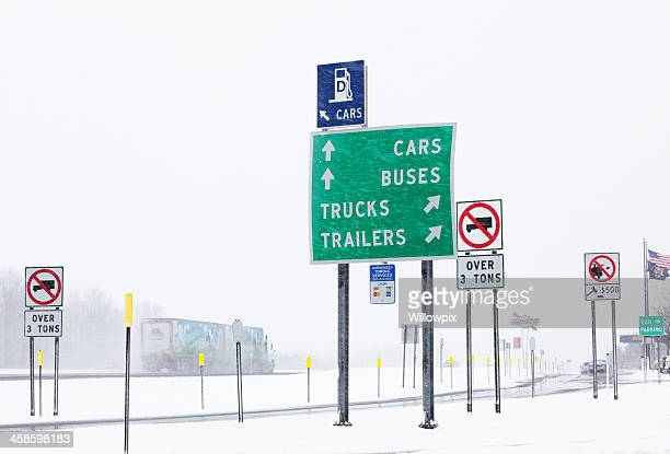 Multiple Signs at Thruway Rest Stop in Winter Blizzard