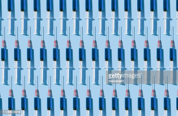 multiple syringes organized in a pattern over blue background - syringe stock pictures, royalty-free photos & images