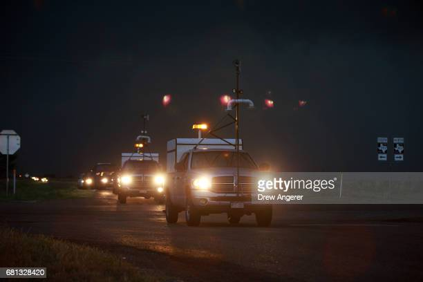 Multiple tornado scout vehicles drive down the road as they chase a supercell thunderstorm as it bears down on the area May 9 2017 in Lamb County...