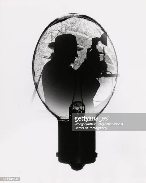 Multipleexposure image shows a silhouette of American photographer Arthur Fellig known popularly as Weegee as seen inside a camera flashbulb early to...