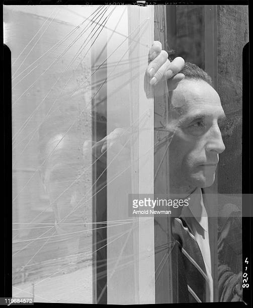 Multiple-exposure portrait of French-born artist Marcel Duchamp as he leans against a door to his 'First Papers of Surrealism' exhibition at the...
