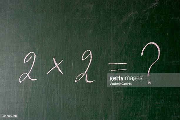 A multiplication problem on a chalkboard with a question mark