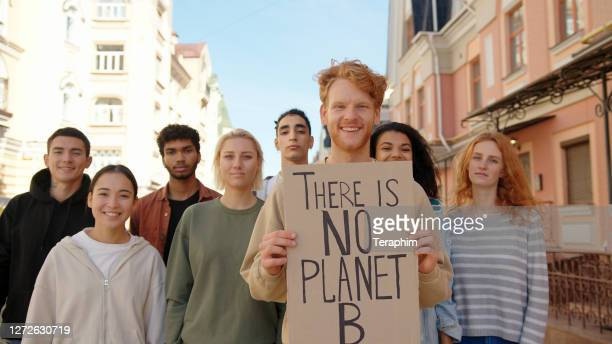 multiracial activists protest supporting ecology and clean planet - slogan stock pictures, royalty-free photos & images