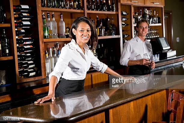 Multiracial bartenders working behind bar counter in restaurant