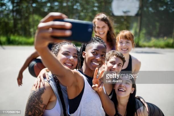 multiracial basketball team taking selfie on court - generation z stock-fotos und bilder