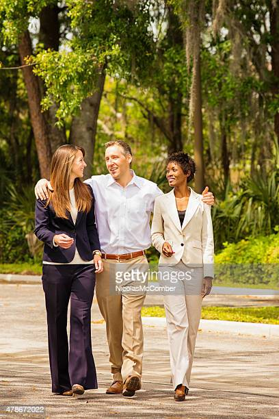 Multi-racial business team of three arriving to work full length