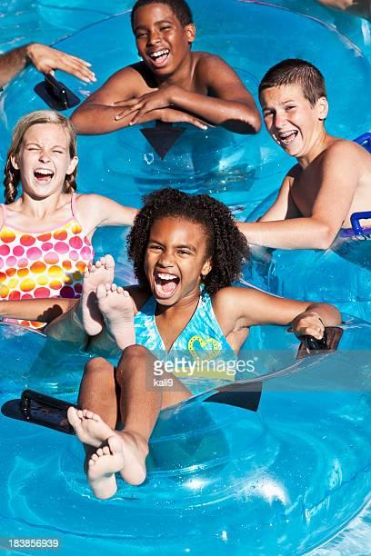 Multiracial children floating on innertubes at water park