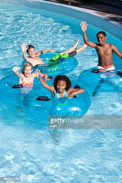 Multiracial children on innertubes at water park