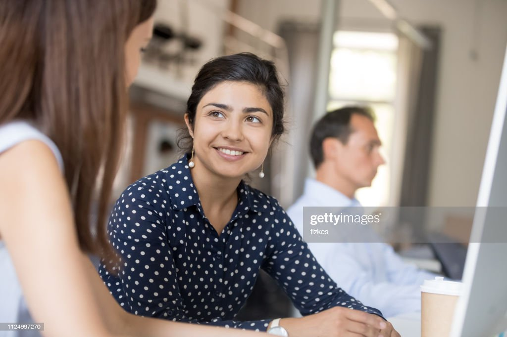 Multiracial colleagues communicating sitting in office at the desk : Stock Photo