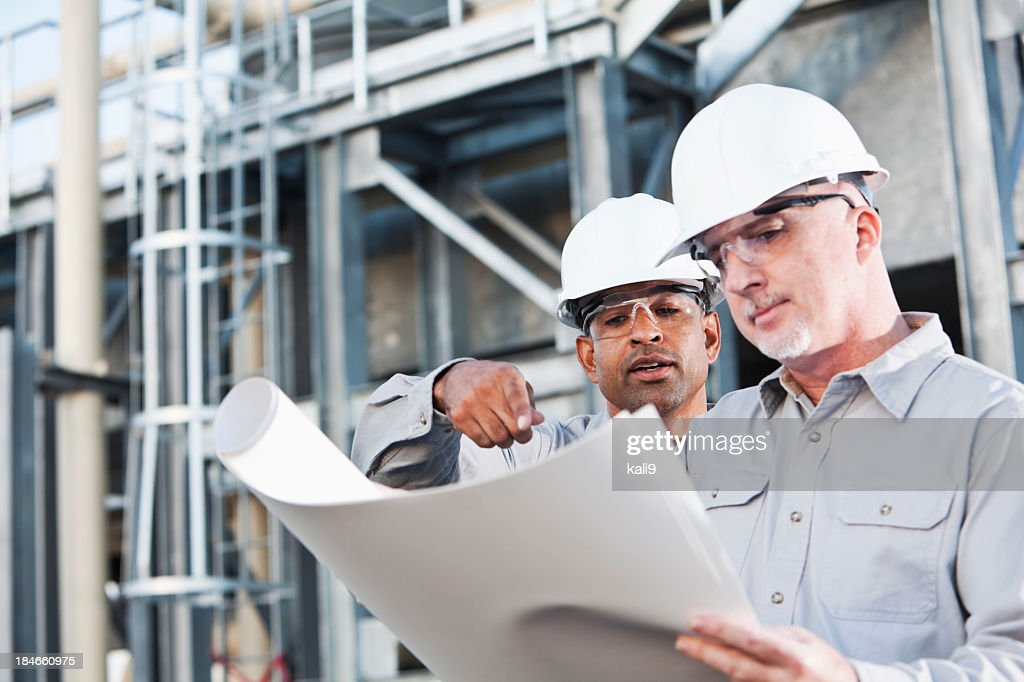 Multiracial engineers at industrial site reading plans : Stock Photo