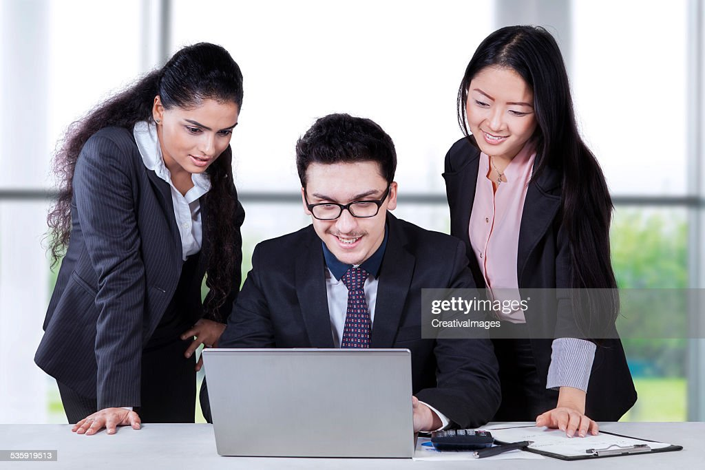 Multiracial entrepreneurs using laptop : Stock Photo